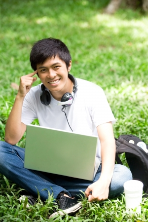 adults learning: Young handsome Asian student has an idea with laptop and smile in outdoor