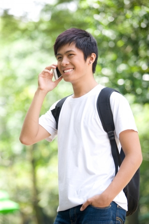 Young handsome Asian student answer phone call and smile in outdoor photo