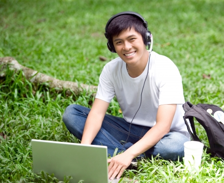 Young handsome Asian student learning with laptop and smile in outdoor photo