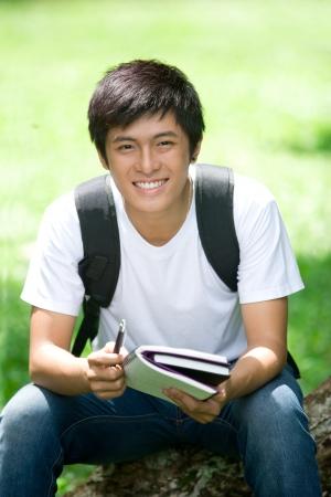 handsome student: Joven estudiante asi�tico apuesto abrir un libro y una sonrisa en el exterior