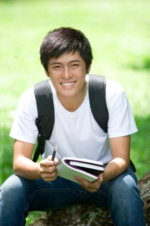 Young handsome Asian student open a book and smile in outdoor photo