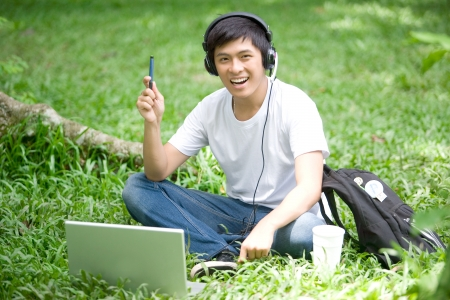 typing man: Young handsome Asian student has an idea with laptop and smile in outdoor