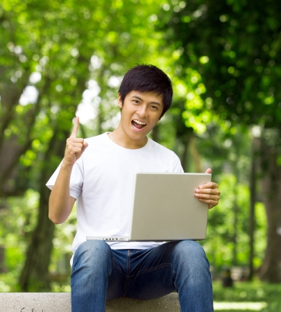 Young handsome Asian student has an idea with laptop and smile in outdoor photo