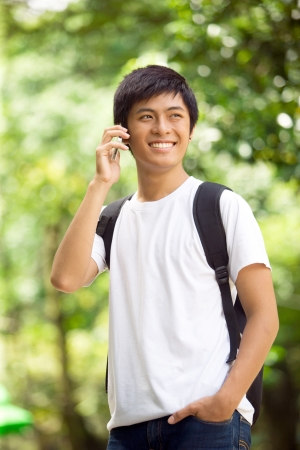 Young handsome Asian student talking on the phone call and smile in outdoor photo