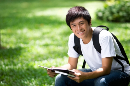 male student: Young handsome Asian student thinking and smile in outdoor Stock Photo