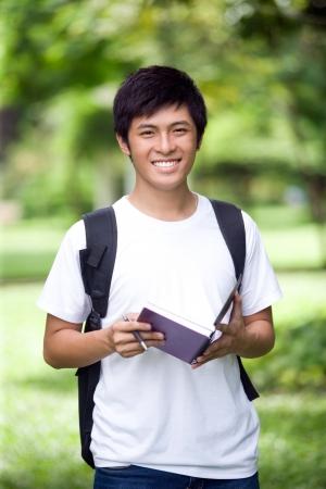 estudiantes universitarios: Joven apuesto estudiante asi�tico libro abierto y una sonrisa en el exterior Foto de archivo
