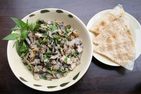 Asian traditional stew vegetarian food with tofu, mushroom, fig, mint, peanut, rice cracker in a ceramic clay bowl photo