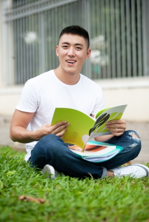 adult vietnam: Young handsome Asian student open a book and smile in outdoor