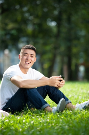 Portrait of young handsome asian student using mobile phone in the park photo