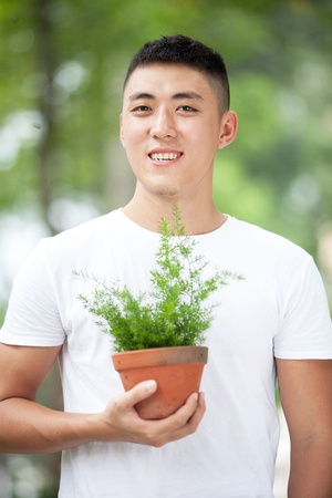 Portrait of young handsome asian student with a plant in clay pot photo