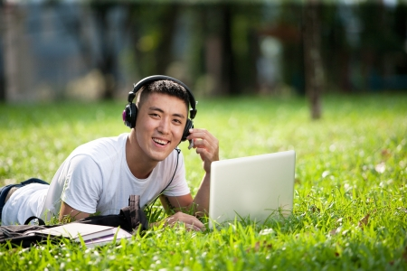 Portrait of young handsome asian student using laptop in the park, smile