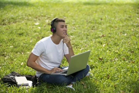 adult vietnam: Young handsome Asian student with laptop and headset out door Stock Photo