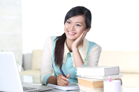 chinese adult: Young girl studying with text book