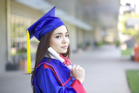 portrait of a beautiful young asian woman in graduation cap in campus photo
