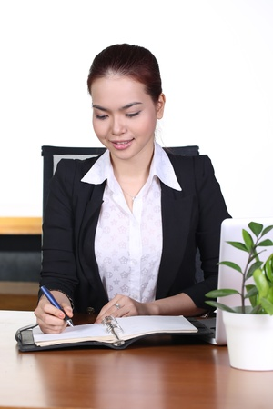 Young business woman working at office, writing on notebook photo