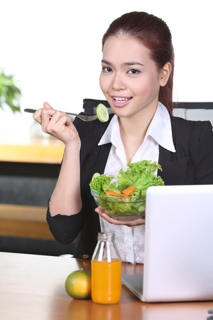 Young businesswoman eating salad as a snack in the office photo
