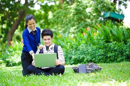 Young asian college student using laptop in the park Stock Photo