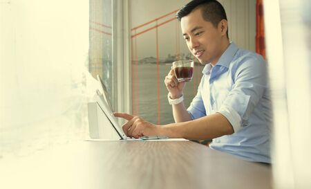 working at home: Asian casual business man working in coffee shop Stock Photo