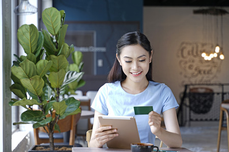 Asian pretty attractive woman sitting in coffee shop using smart phone