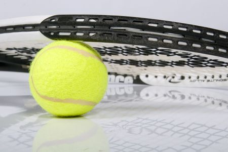 Tennis ball with a detailed racquet lying on it photo
