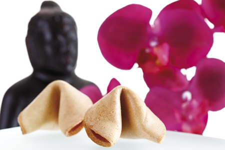 Fortune cookies, buddha head and orchid leaves in background photo