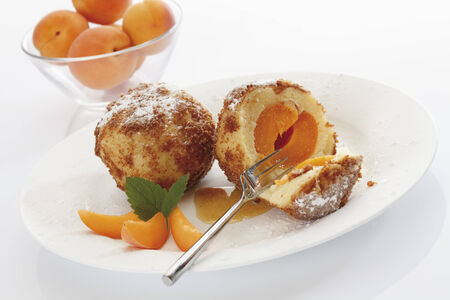 Apricot dumpling breaded, served on plate,in the background bowl filled with apricots  photo