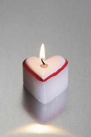 Heart-shaped lighted candle photo