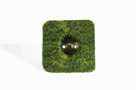 Plug socket with grass against white background photo