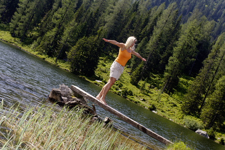 Young woman standing on wooden plank at lake photo