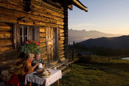 mountain hut: Mature couple sitting in front of alpine hut, watching sunset