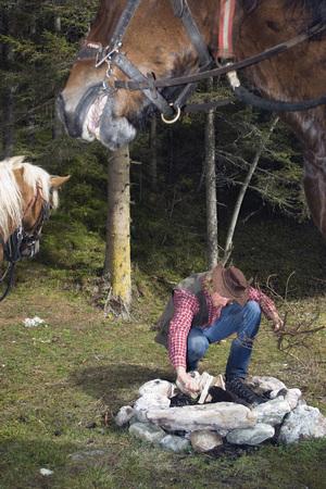 Austria, Salzburger Land, Altenmarkt, Young man preparing campfire