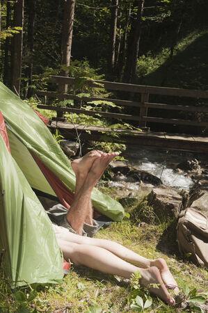 steiermark: Austria, Steiermark, Young couple lying in tent by stream