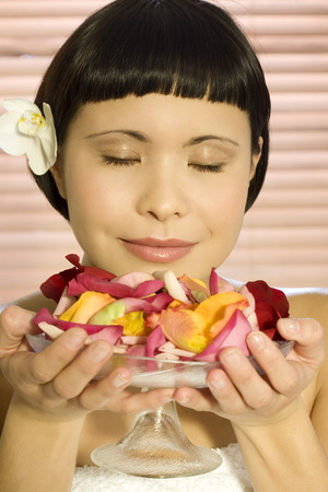 Young woman holding bowl of rose petals, eyes closed