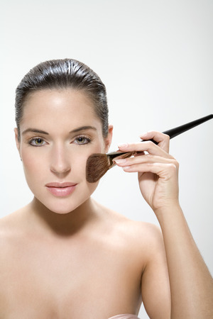 slicked: Young woman using make up brush, portrait