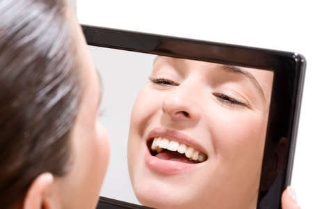 Young woman looking into mirror, smiling, portrait photo
