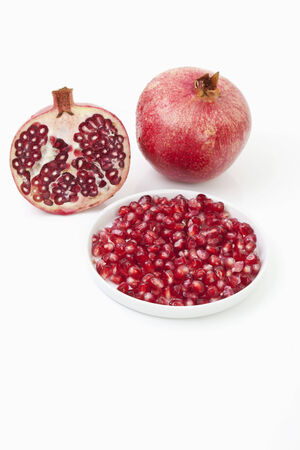Pomegranate, whole fruit, half and the seeds photo