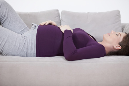 Pregnant woman lying on couch, eyes closed Stock Photo