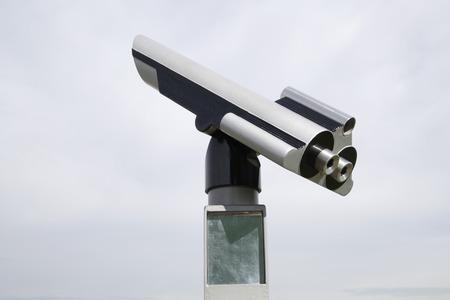 Telescope against cloudy sky, close up photo