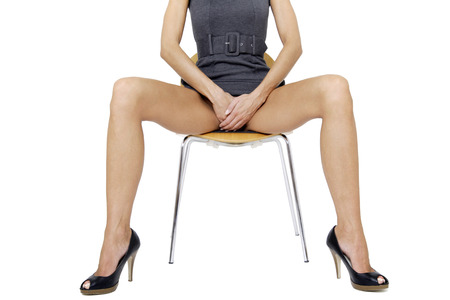 legs open: Young woman in mini dress sitting on chair, middle section Stock Photo