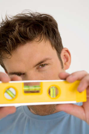 spirit level: Young man with yellow spirit level, close-up