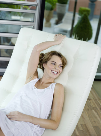 reclining chair: Woman relaxing on reclining chair, smiling, elevated view Stock Photo