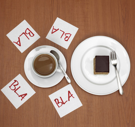 Cup of coffee, cake and slips of paper on table Stock Photo