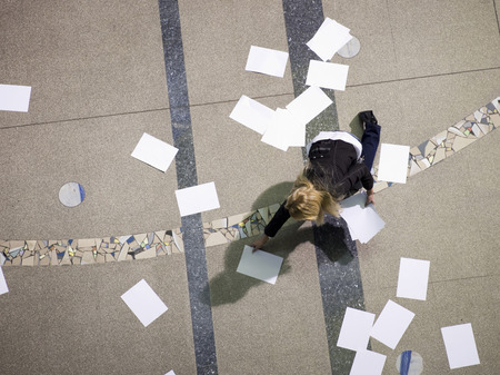 Businesswoman in hall picking up papers photo