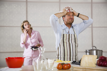 overstress: Man cooking woman standing in background Stock Photo