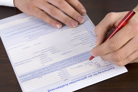 left handed: Man filling in form Stock Photo