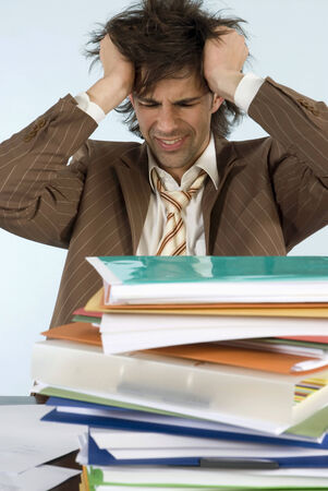 overstress: Man sitting on desk with stack of files