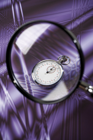 depth measurement: Stop watch under magnifying glass Stock Photo