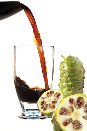 Juice from Noni fruit flowing into cocktail glass photo