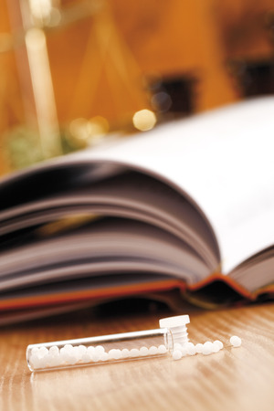Homeopathic remedy in front of homeopathic book, close-up photo