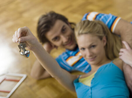 Couple lying on floor holding keys photo